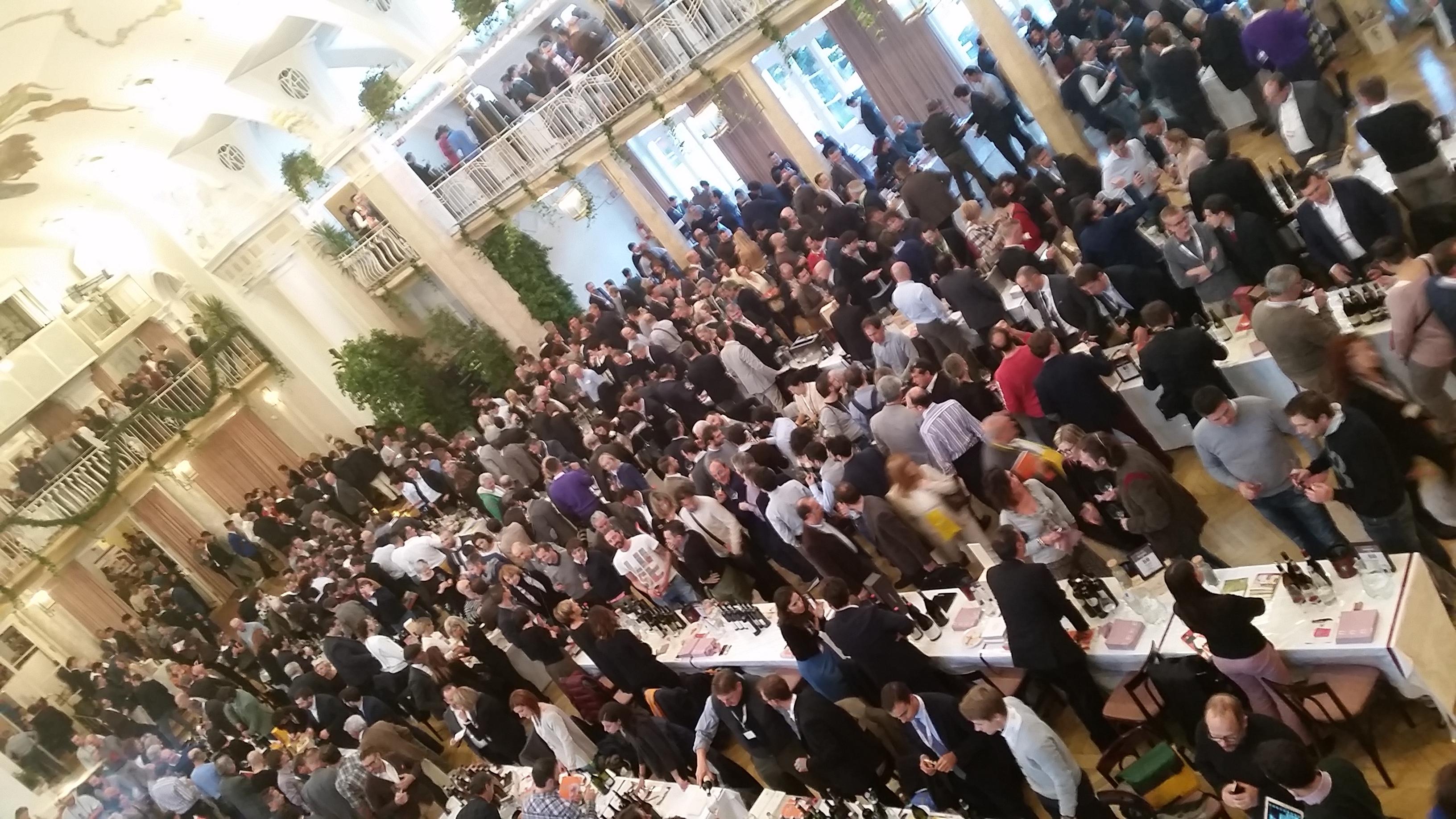 Persone radunate dentro alla location del Festival di Merano degustando vino
